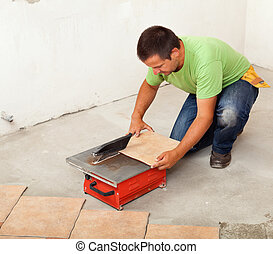 Man cutting ceramic floor tile - knealing by a cutter ...