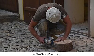 Man cutting ceramic tile with angle grinder - Close up of...