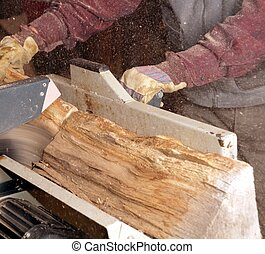 Man cutting Firewood with circular saw
