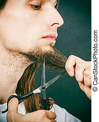Man cutting his beard