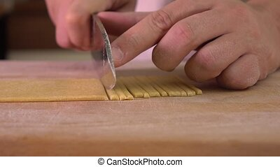 Man cutting homemade pasta with a knife. Amateur cooking at...
