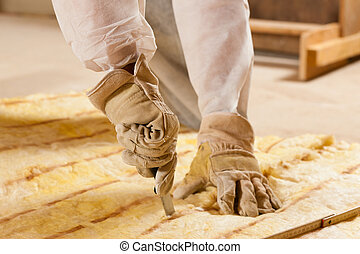 Man - only hand to be seen - cutting some glass wool as material for thermal insulation of a new building