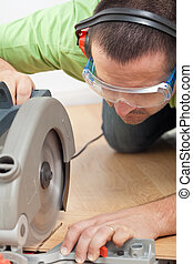 Man cutting laminate floor plank