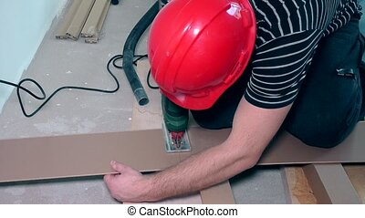 Man cutting laminate flooring with electric hand saw....