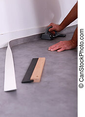 Man cutting lino to fit against a skirting board