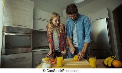 Man cutting orangesin the kitchen.