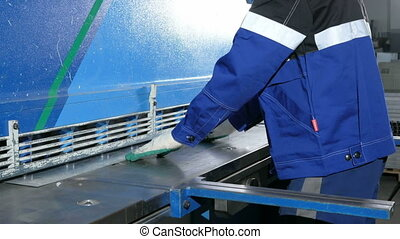Man cutting sheet metal in large hydraulic guillotine...