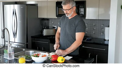 Man cutting vegetable in kitchen 4k - Man cutting vegetable...