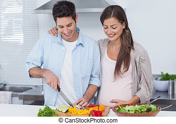 Man cutting vegetables next to his pregnant partner