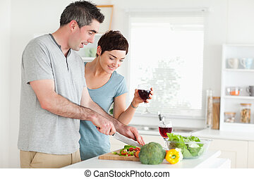 Man cutting vegetables while is woman is watching