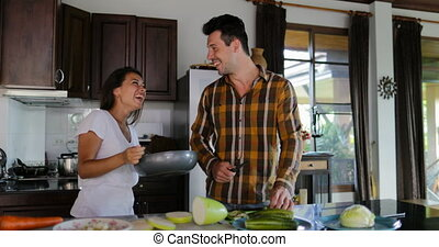 Man Cutting Vegetables, Woman With Frying Pan Preparing Healthy Dinner Couple In Kitchen Cooking Together Talking Happy Smiling