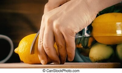 Man cutting whole lemon and making juice with a juicer....