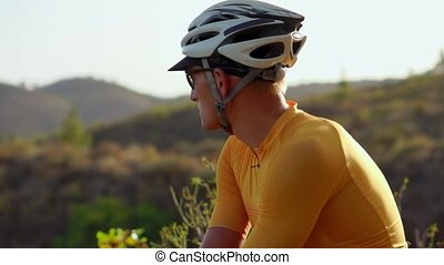 Man cyclist resting after arrival and admiring the view of the mountains
