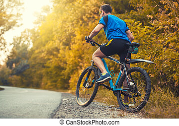 man cyclist rides in the forest on a mountain bike.