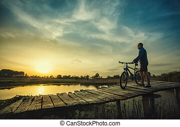 man cyclist Rides on a wooden bridge across the river - The...