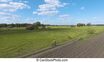 cyclist rides on the spring green meadow - man cyclist rides...