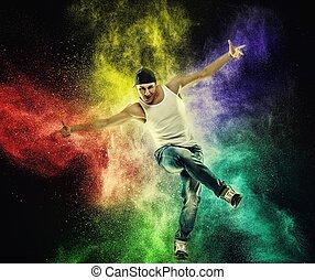 Man dancer showing break-dancing moves against colourful powder explosion