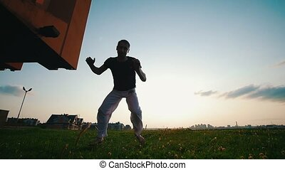Man dancing capoeira, throwing back his legs, flies up in the air, summer evening, at sunset