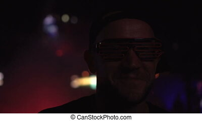 Man dancing in the club wearing neon led glasses