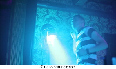Man dancing in the night club. Spotlight. By turns illuminates the lights
