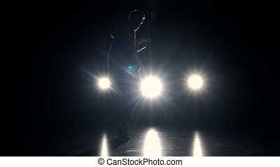 Man dancing on stage - Man performing a modern dance on dark...