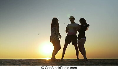 Man dancing with two women on the beach at sunset