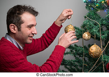 Man decorating a christmas tree with golden balls
