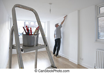 decorating - man decorating a room with ladder and paint pot...