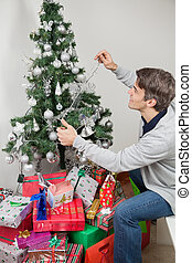 Man Decorating Christmas Tree With Fairy Lights At Home