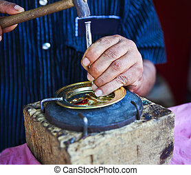 Man decorating golden plate with narrow focus - Man's hands ...