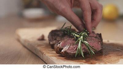 man decorating sliced medium rib eye steak with rosemary branch, wide photo