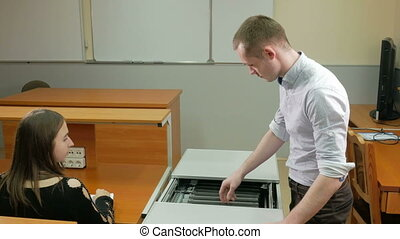 Man delivers laptops class university in a special box. He pulls out and puts on the table the woman. She runs the computer. Mobile Charging and Storage Cart.