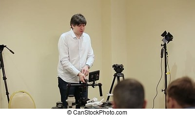 Man demonstrating electronic gimbal steadicam with camera