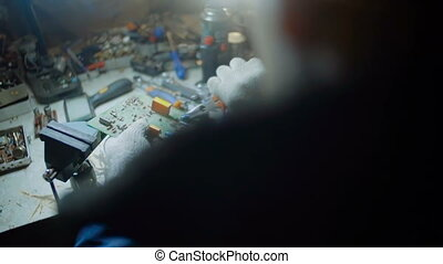 Man Demount the Electronic Circuit Board Apart with Pliers