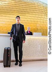 Man departing on business trip at hotel reception