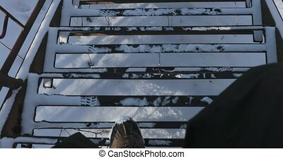 Man descends the iron stairs in winter. POV video 4k