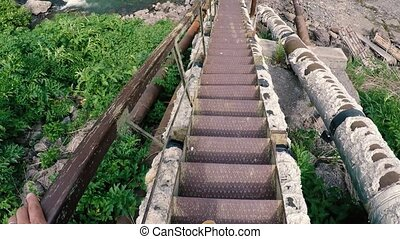 man descends the long metal staircase across the Arpa River, Armenia