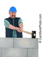 Man destroying wall with sledge-hammer