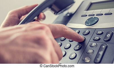 Man dialling out on a landline telephone pressing the number...