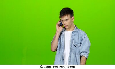 Guy holds the phone in his hands and dials a familiar number and begins to talk angry and nervous. Green screen