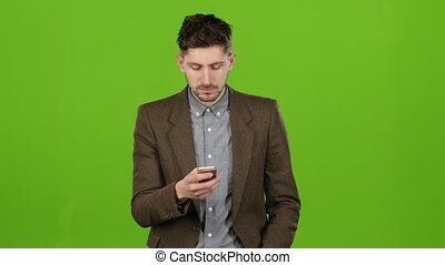 Man holds a phone in his hands and dials a familiar number and starts talking and smiling. Green screen