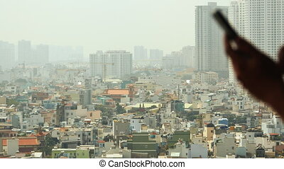 Man dials the phone against the backdrop of the city from the window 2