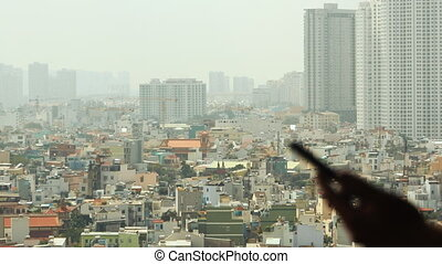 Man dials the phone against the backdrop of the city from the window 3
