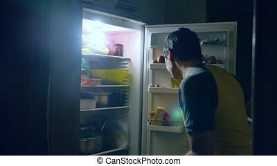 man diet gluttony eats at night from fridge. man opens indoors refrigerator and fridge