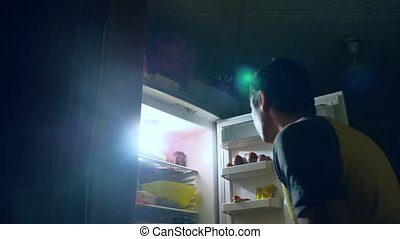 man diet gluttony eats at night from fridge. man opens refrigerator indoors and fridge