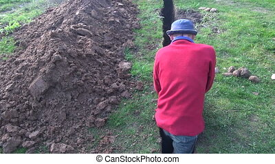 Man digging a very narrow ditch - Builder worker with red...