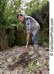 Man digging soil with spade