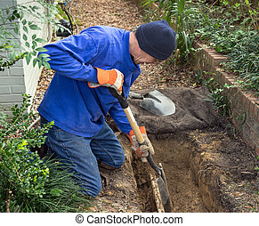 Man digging trench to replace old sewer pipes and lawn sprinkler system line.
