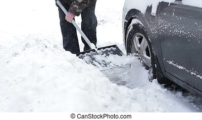 Man digs out his car from the snow.