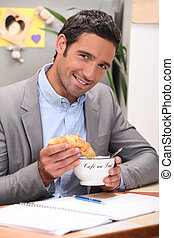 Man dipping croissant into coffee